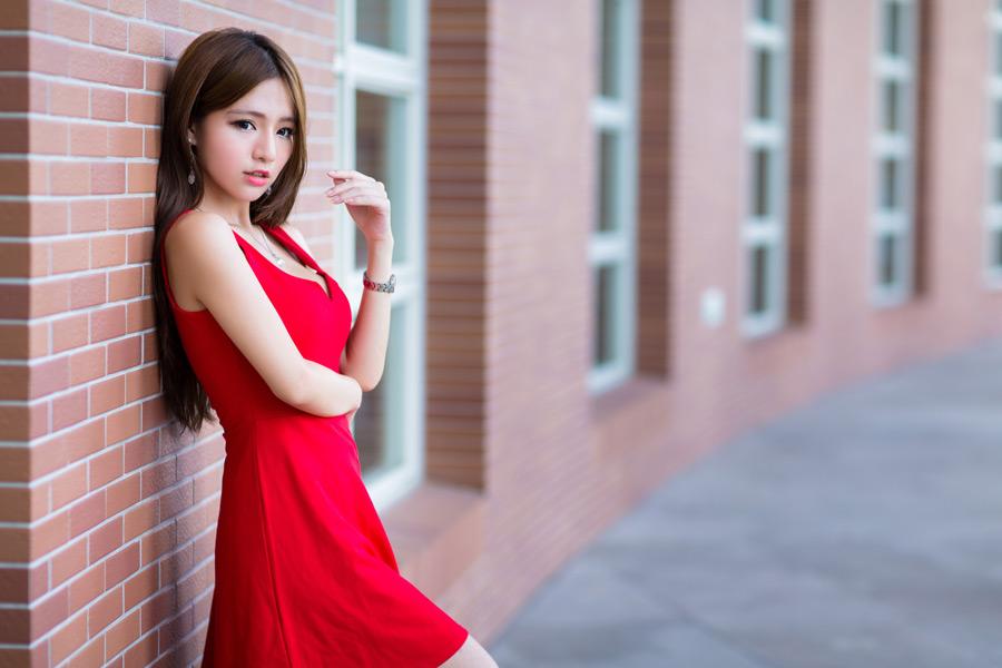 フリー写真 ドレス姿で壁にもたれかかる女性