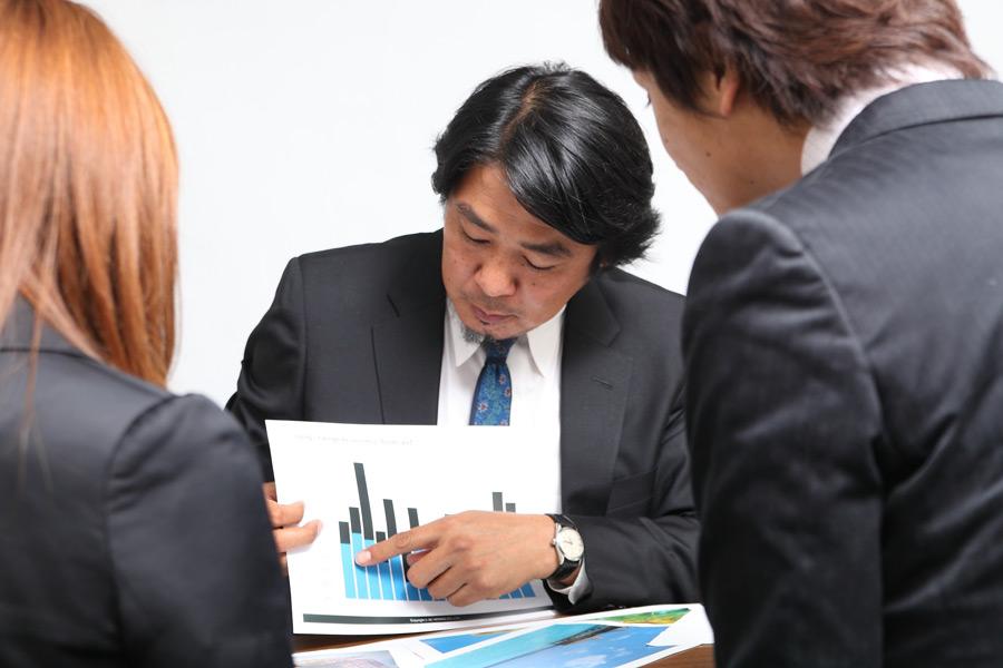 フリー写真 データを指差しながら会議中の上司と部下