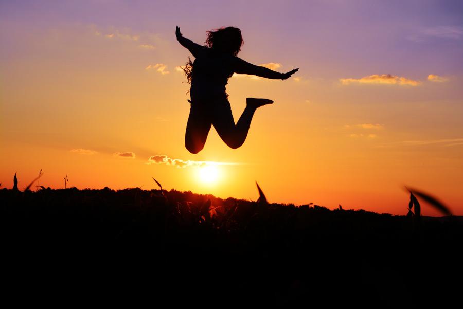 フリー写真 夕陽をバックにジャンプする人物のシルエット