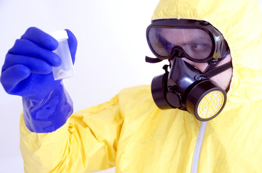 フリー写真 防護服とガスマスク姿で密閉容器を見る科学者