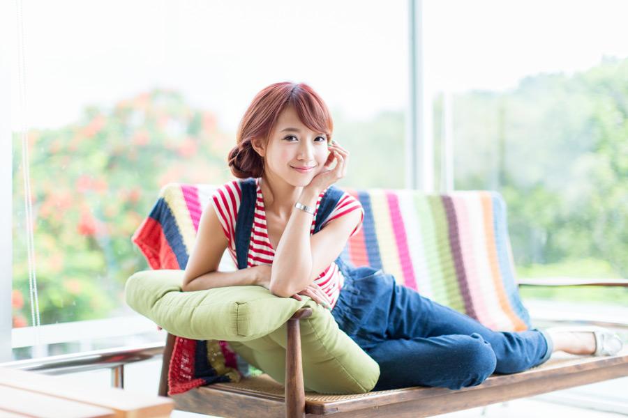 フリー写真 ベンチに上で顎に手を当てる女性のポートレイト