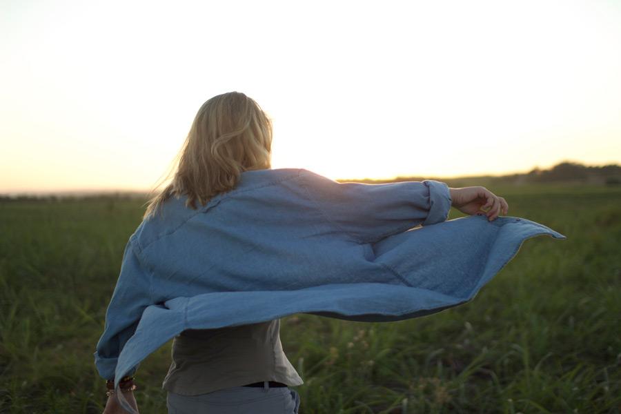 フリー写真 草むらでシャツの裾を広げる女性の後ろ姿