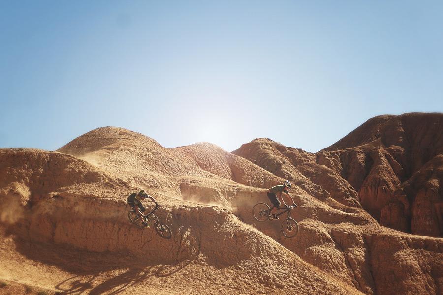 フリー写真 岩山をマウンテンバイクで駆ける二人