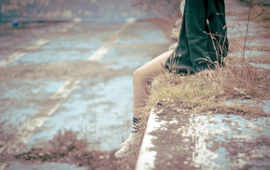 フリー写真 廃墟となったプールの脇に座る女性