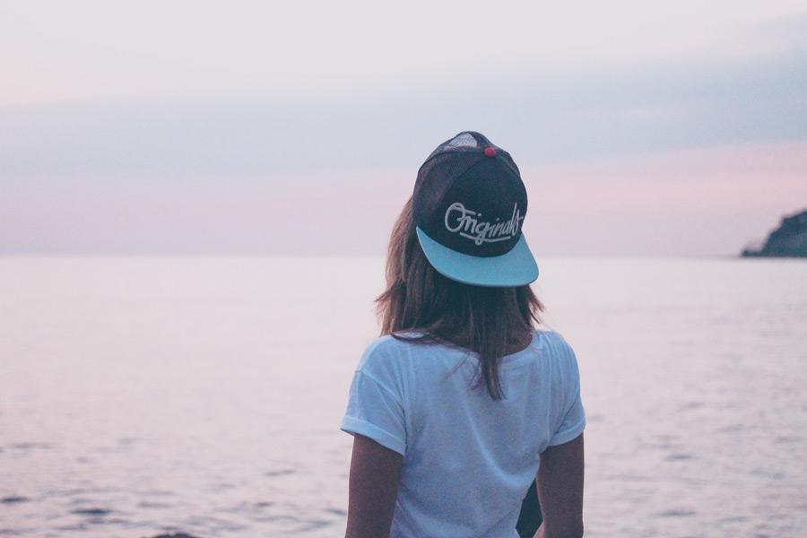フリー写真 キャップを被って海を眺める女性の後ろ姿