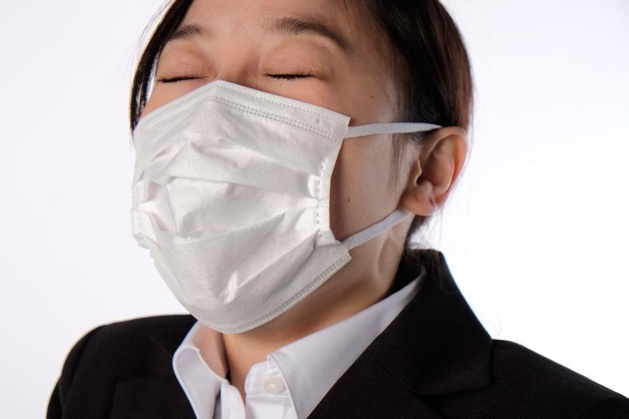 フリー写真 マスクをしてくしゃみをする寸前のビジネスウーマン