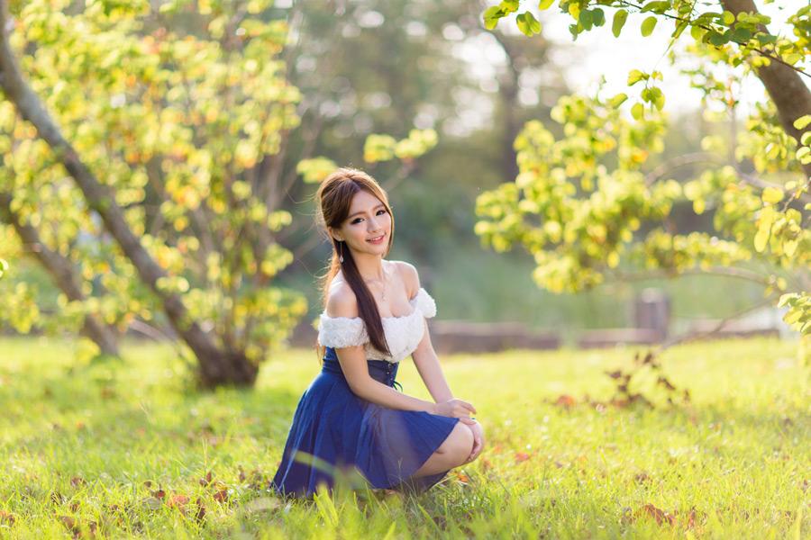 フリー写真 芝生の上にしゃがんでいる女性のポートレイト