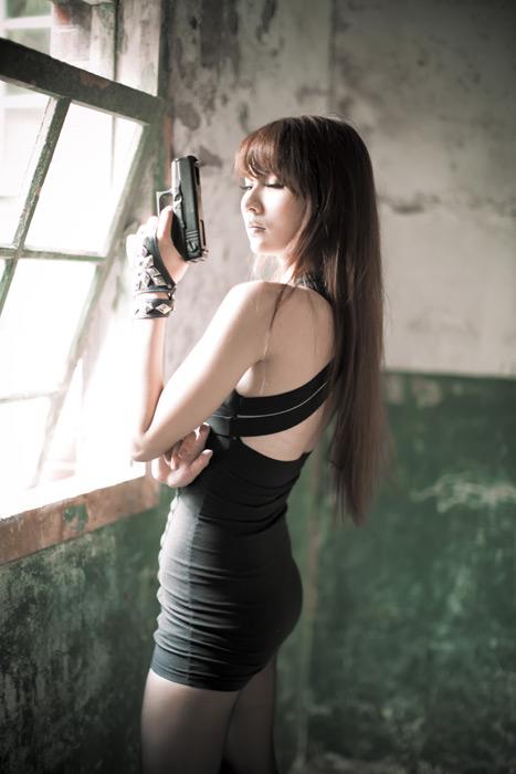 フリー写真 窓辺で拳銃を持つ女性のポートレイト