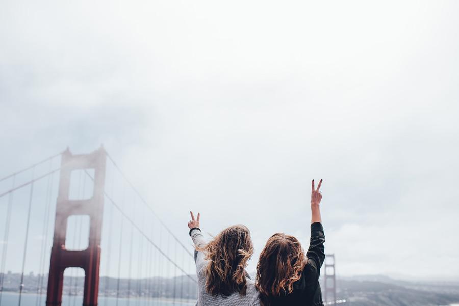フリー写真 ゴールデンゲートブリッジとピースサインの二人の女性
