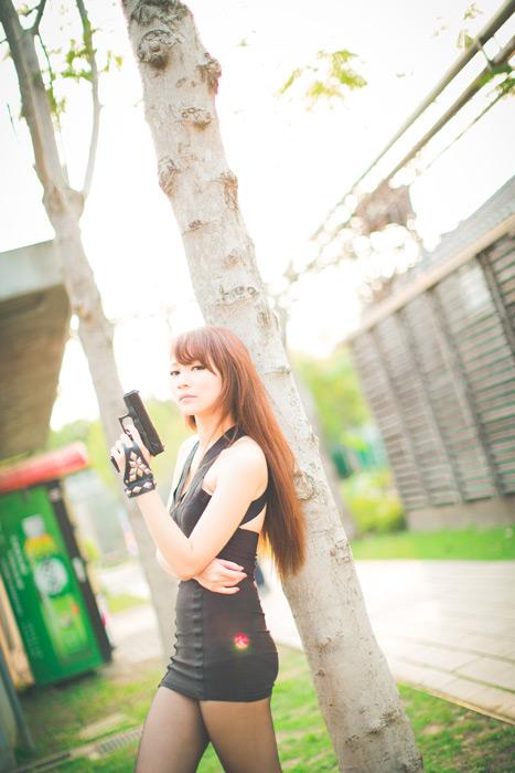 フリー写真 拳銃を持って木に寄りかかる女スパイ