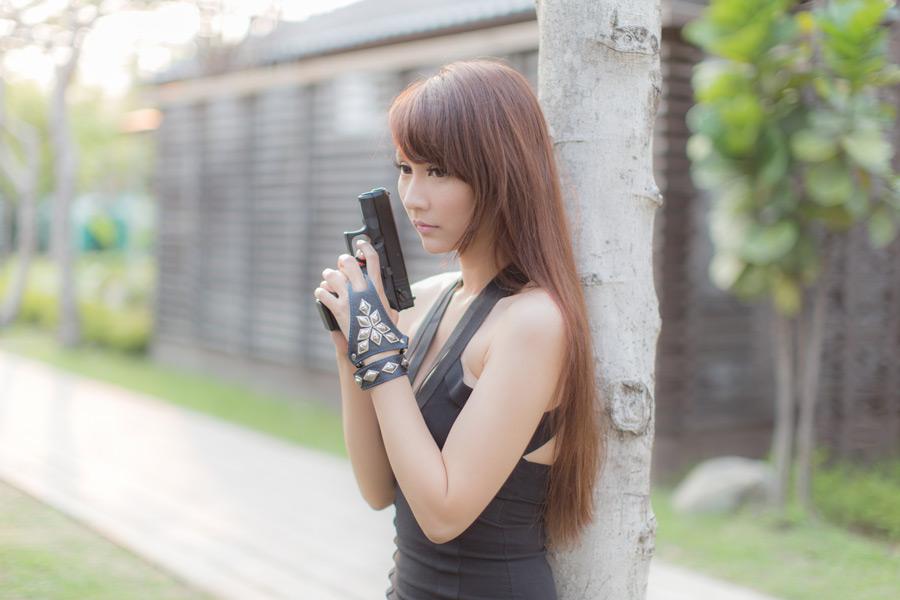 フリー写真 両手でピストルを持っている女性スパイ