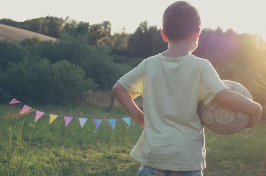 フリー写真 サッカーボールを抱える男の子の後ろ姿
