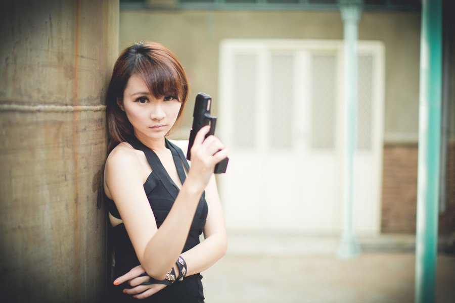 フリー写真 ピストルを持って壁に寄りかかる女性スパイ