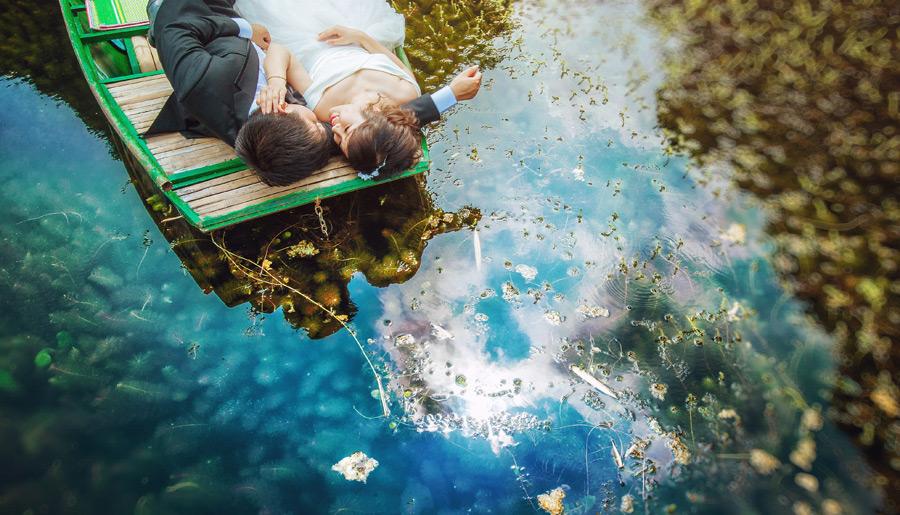 フリー写真 舟の上で寝転ぶ新郎新婦