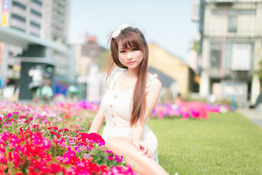 フリー写真 花壇の花の前に座る女性