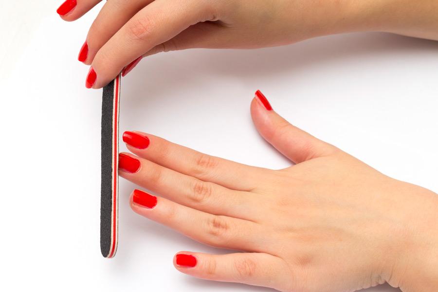 フリー写真 爪やすりで爪を研ぐ女性の手