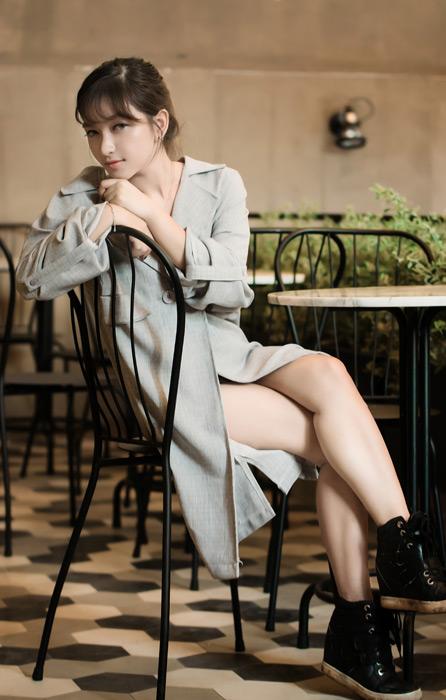 フリー写真 コート姿で足を組んで座る女性のポートレイト