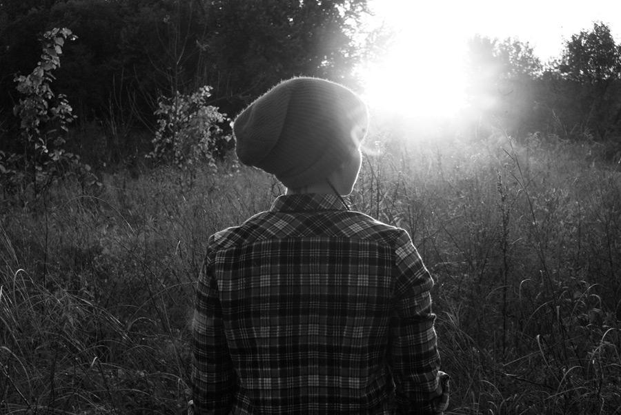 フリー写真 太陽光と草むらに立つ女性の後ろ姿