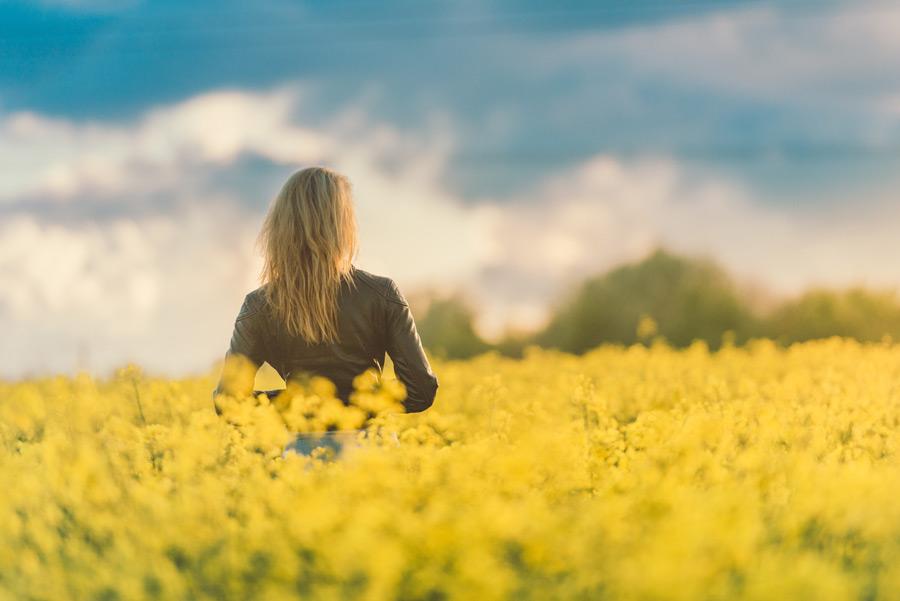 フリー写真 菜の花畑に立つ外国人女性の後ろ姿