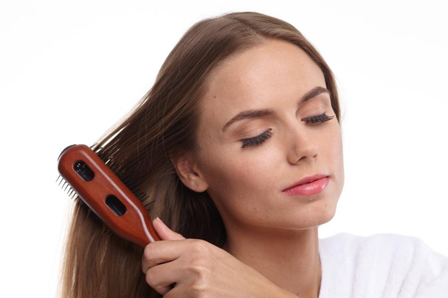 フリー写真 ヘアブラシで髪の毛をブラッシングする女性