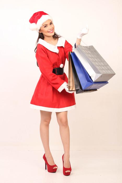 フリー写真 サンタの衣装姿でショッピングバッグを持つ女性