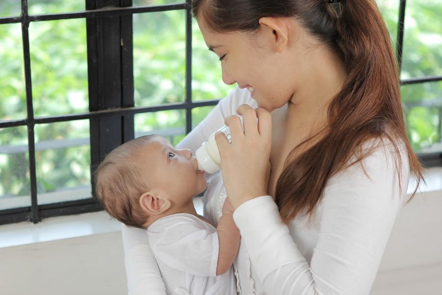 フリー写真 哺乳瓶で赤ちゃんにミルクを与える母親