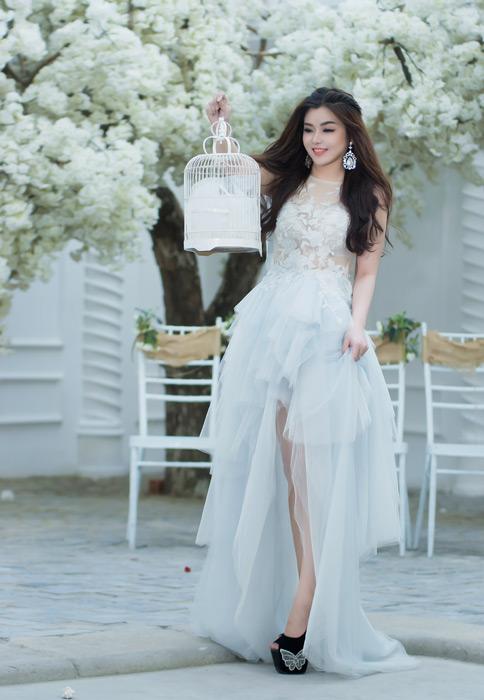 フリー写真 ウェディングドレス姿で鳥かごを見る女性