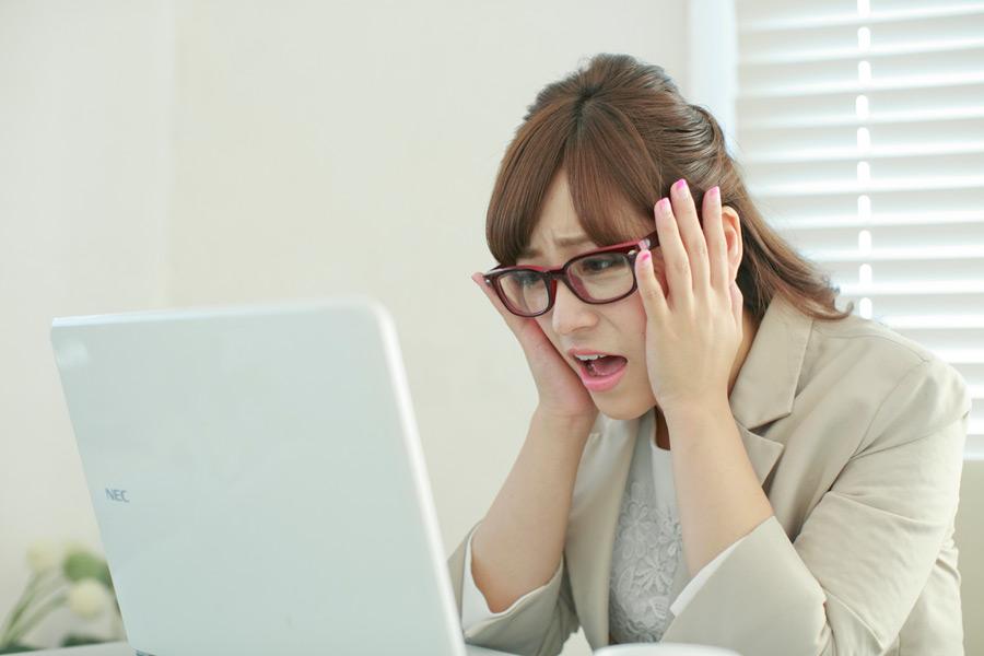 フリー写真 パソコンの前で頭を抱えるビジネスウーマン