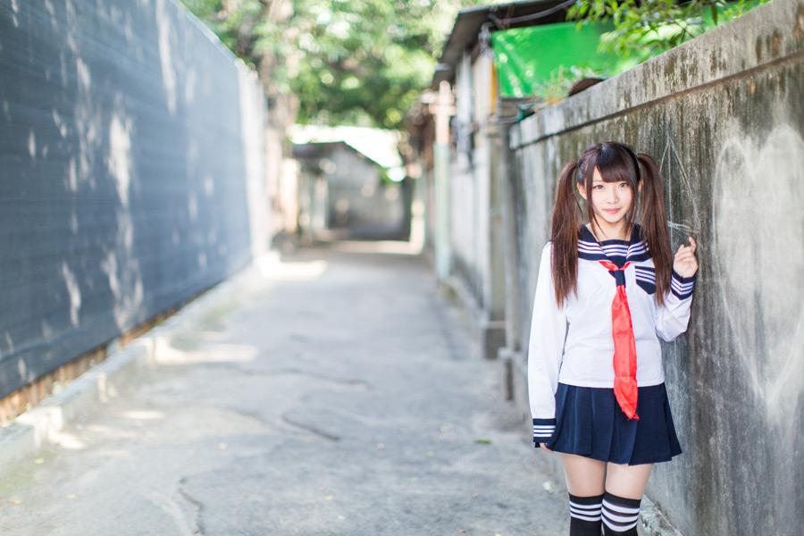 フリー写真 塀の落書きとセーラー服姿の女子高生