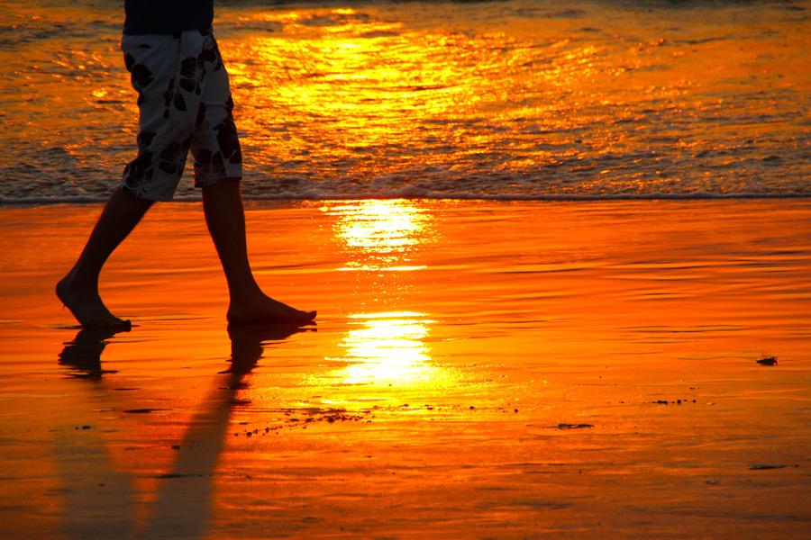 フリー写真 夕日に染まるビーチと脚