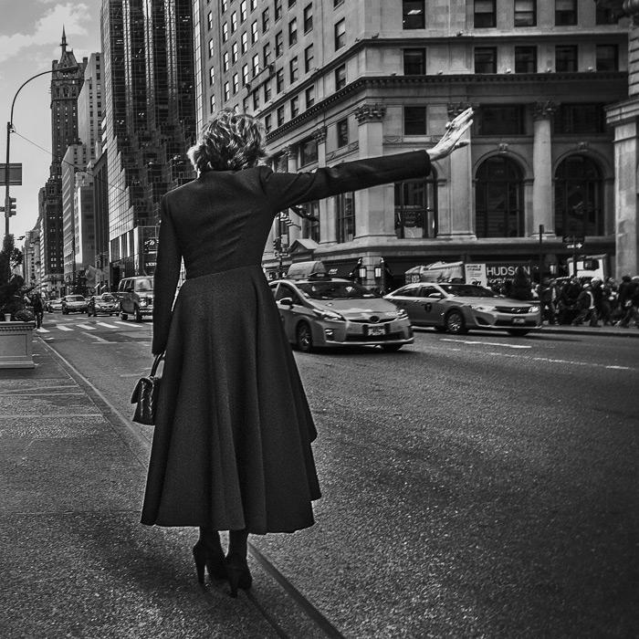 フリー写真 マンハッタンでタクシーを呼ぶ女性の後ろ姿