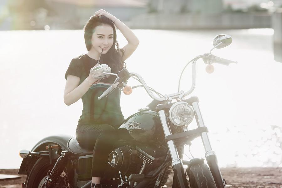 フリー写真 バイクに跨って髪の毛をかき上げる女性