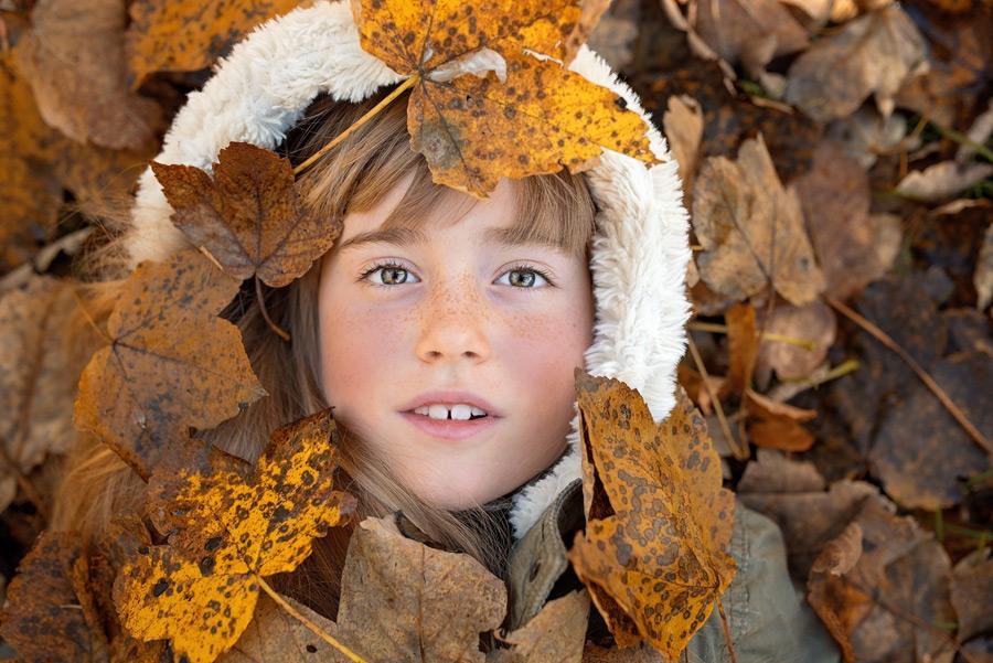 フリー写真 落ち葉に埋もれる外国の女の子