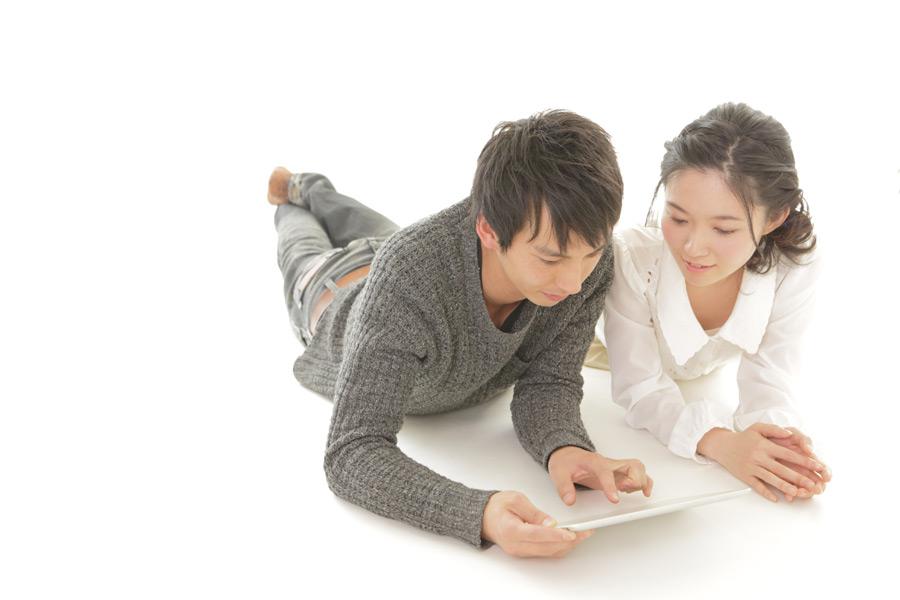 フリー写真 腹這いになってタブレットPCを見ているカップル