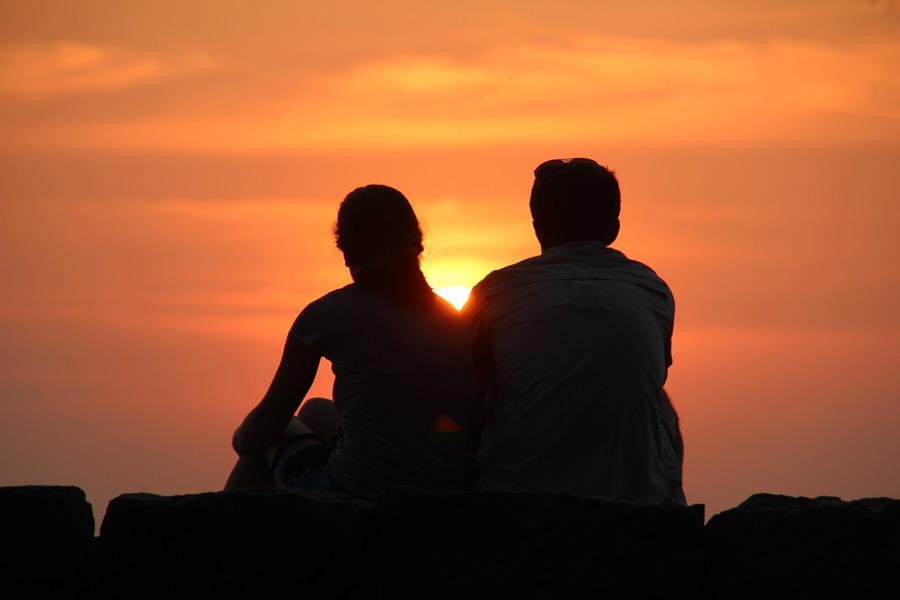フリー写真 夕日を眺めるカップルのシルエット