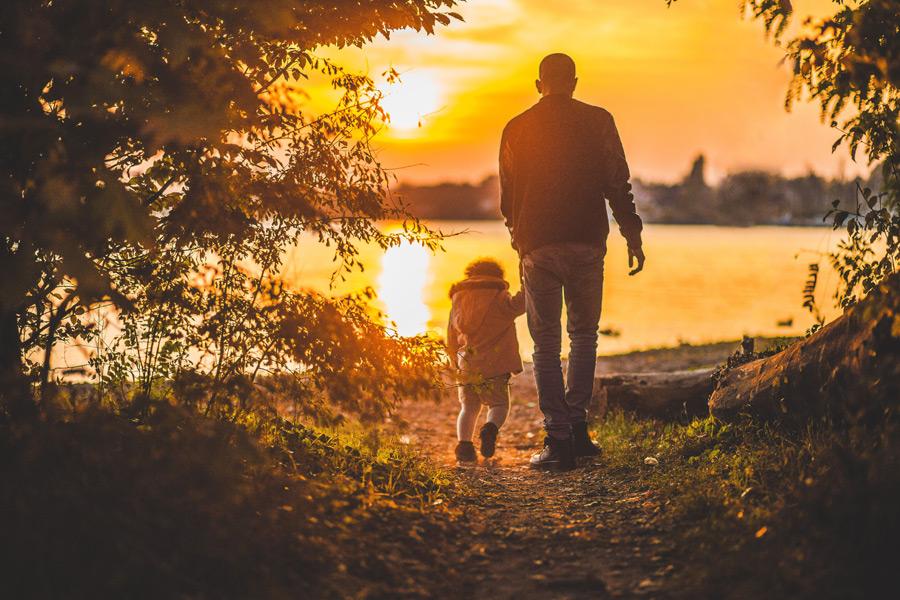 フリー写真 夕陽と手をつないで歩く父と子