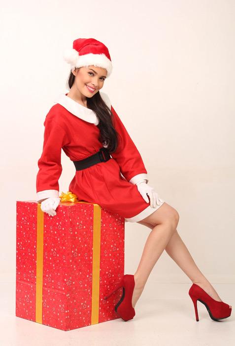 フリー写真 サンタのコスチュームを着てプレゼントの上に座る女性