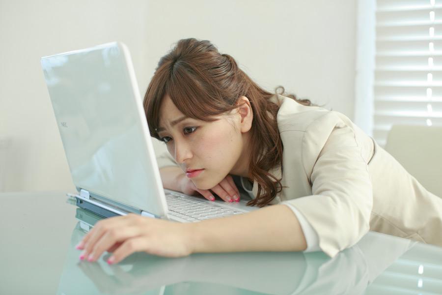 フリー写真 パソコンの前で疲れ果てる女性社員