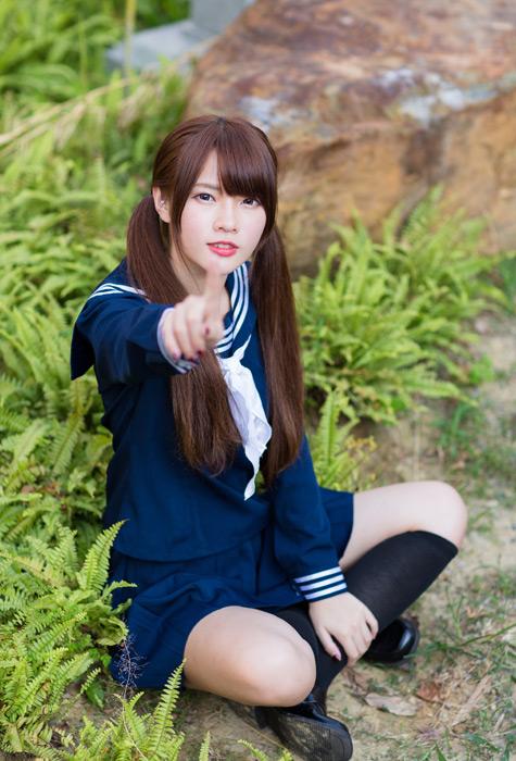 フリー写真 地面に座って手前を指差す女子高生