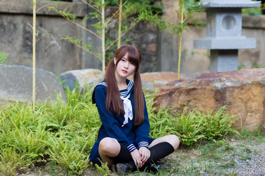 フリー写真 あぐらをかいて地面に座る女子高生