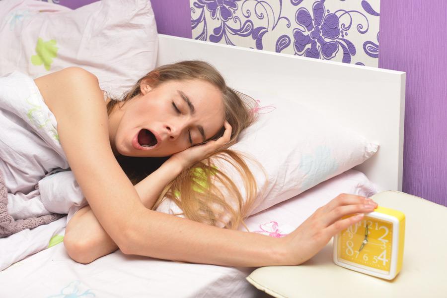 フリー写真 目覚まし時計に起こされる外国人女性