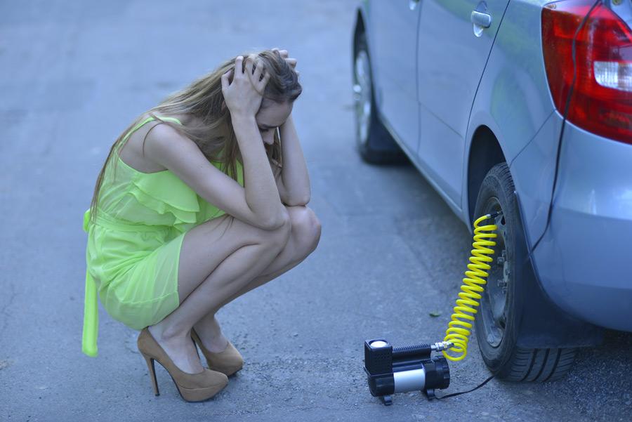 フリー写真 車のパンクに頭を抱える外国人女性