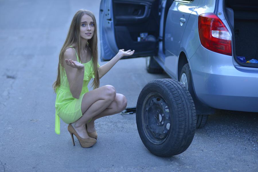 フリー写真 車のタイヤ交換の仕方が分からない外国人女性
