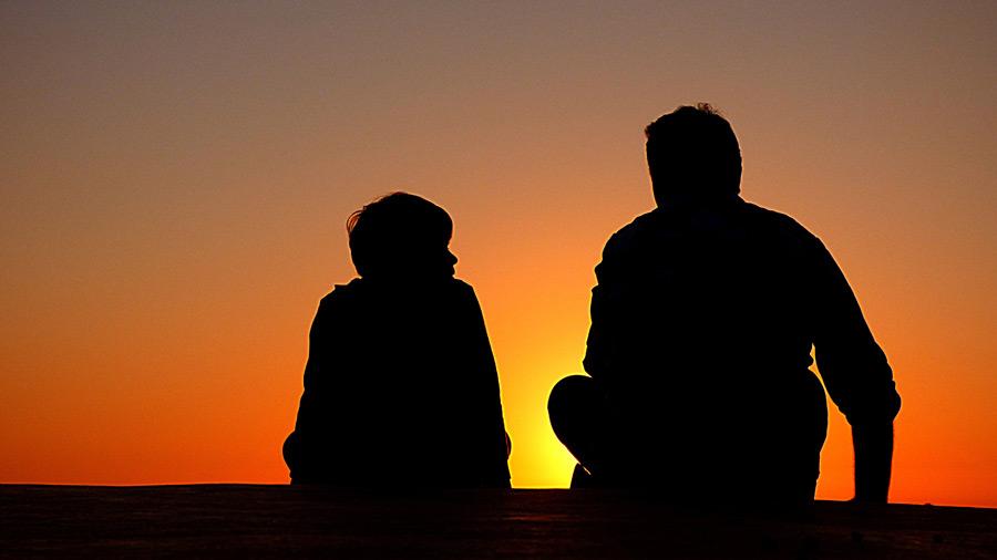 フリー写真 夕焼けの空と父と息子のシルエット