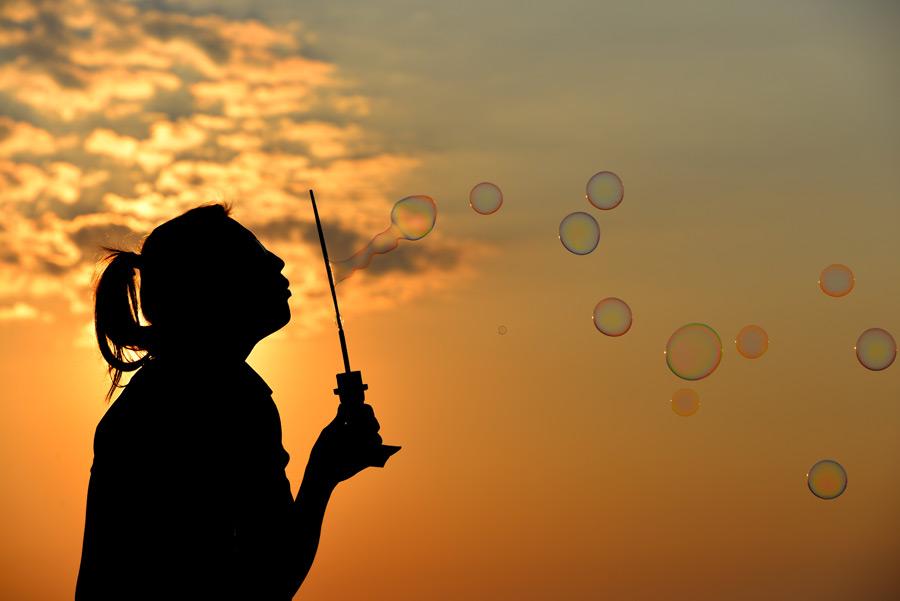 フリー写真 夕焼けとしゃぼん玉で遊ぶ女性のシルエット