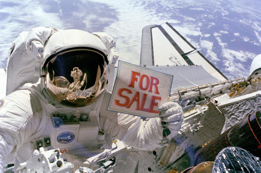 フリー写真 「For Sale」の広告を掲げる宇宙飛行士