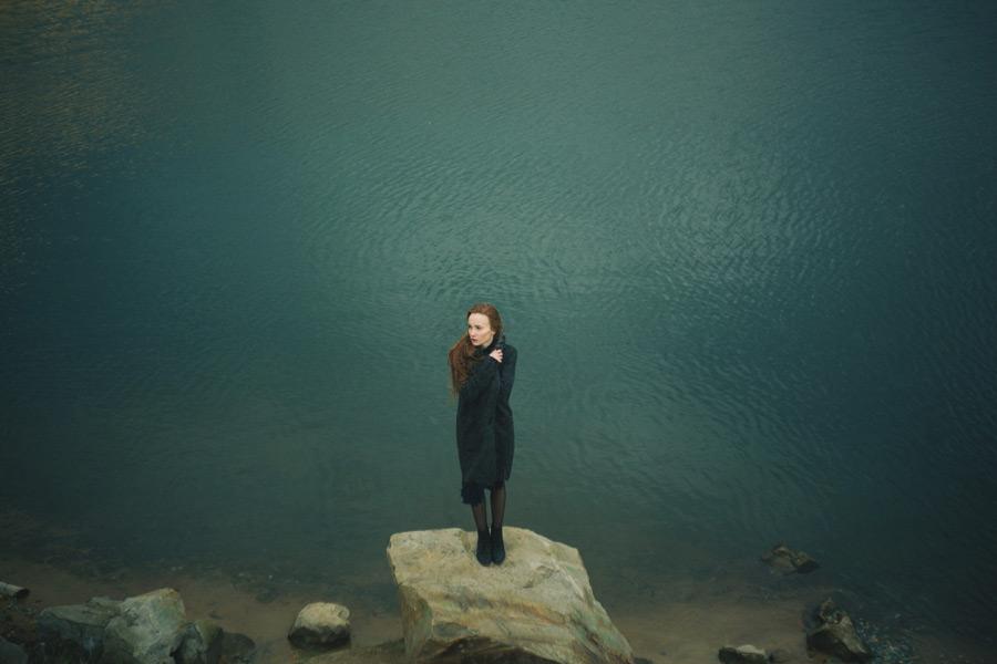 フリー写真 川の前の石の上に立つロシア人女性