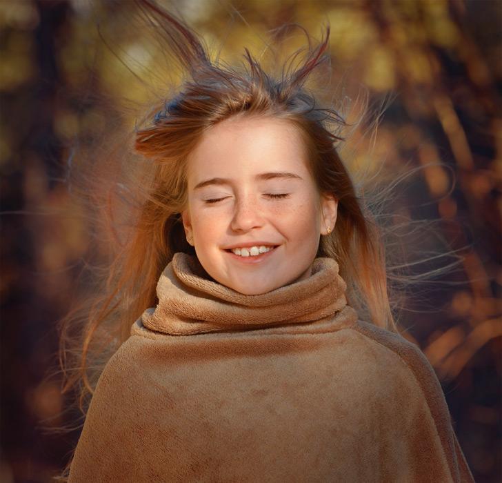 フリー写真 目を閉じて風に吹かれている外国の女の子