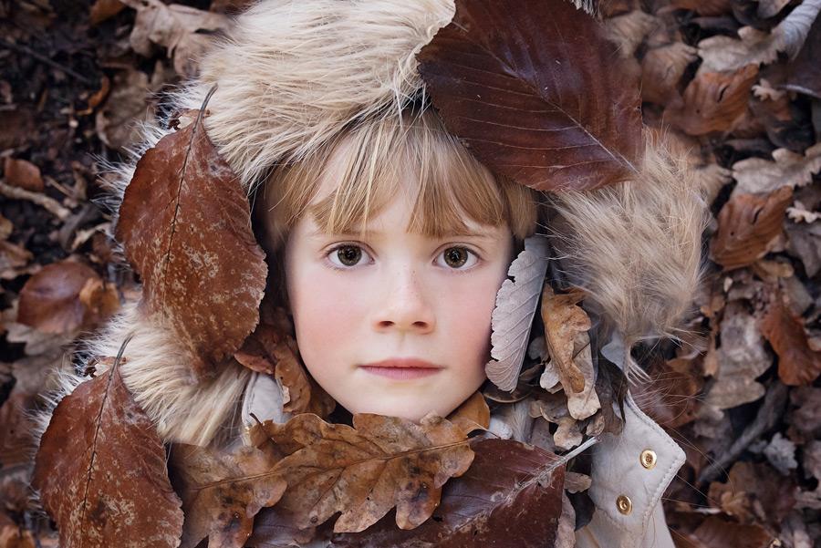 フリー写真 落ち葉に埋もれる女の子の顔