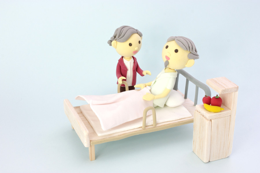 フリー写真 入院したおじいさんを看病するおばあさん